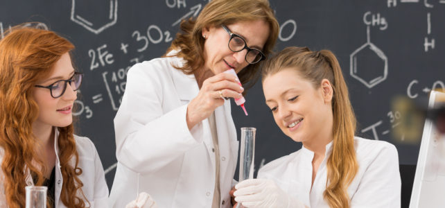 Young female students with elderly professor in lab coats analyzing chemicals using test-tube